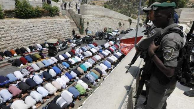 Policías israelíes vigilan mientras docenas de palestinos rezan junto a la Puerta de los Leones de la Ciudad Vieja de Jerusalén, tras negarse a pasar por los nuevos controles de seguridad impuestos en torno a la Explanada de las Mezquitas, en Jerusalén.