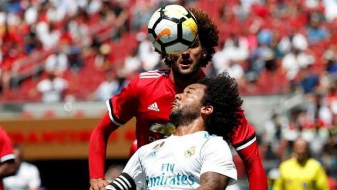 El defensa del Real Madrid Marcelo cabecea el balón frente el mediocampista del Manchester United Marouane Fellaini en partido de la International Champions Cup.