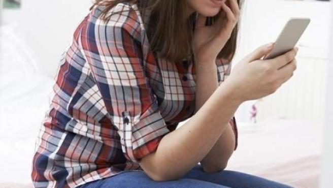 Una adolescente con un móvil.