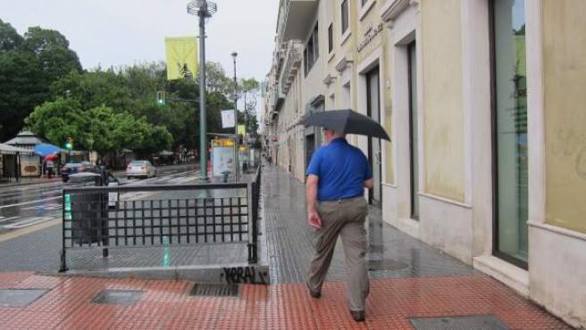 Un hombre se protege de la lluvia con un paraguas.