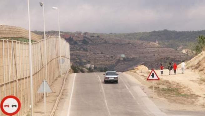 Un grupo de menores circula por las inmediaciones del centro de La Purísima. Al otro lado de la carretera, la valla fronteriza que separa Melilla de Marruecos.