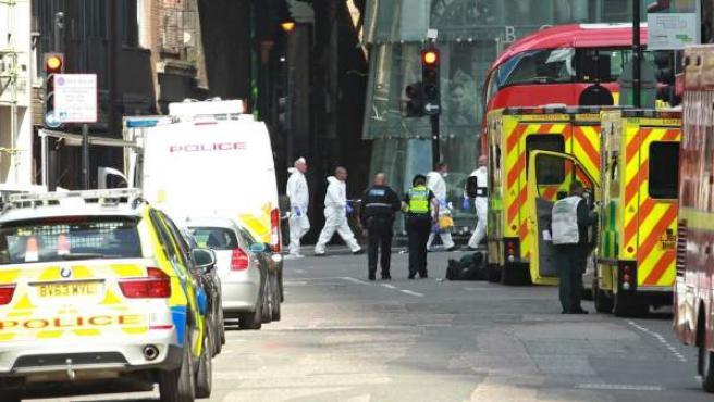 Equipos forenses y agentes de policía trabajan en el puente de Londres, un día después del ataque perpetrado en junio por tres hombres con una furgoneta, que posteriormente abandonaron y comenzaron a acuchillar a viandantes.