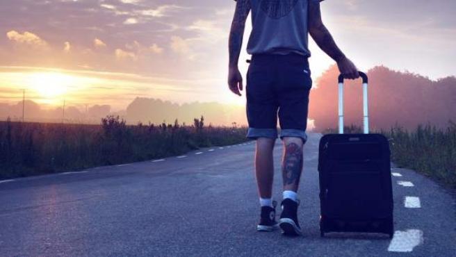 Un chico caminando con su maleta