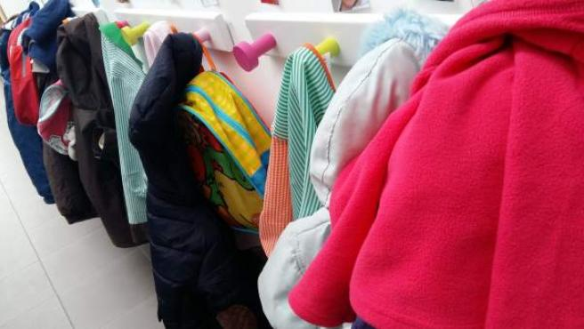 Imagen de abrigos colgados en un aula.