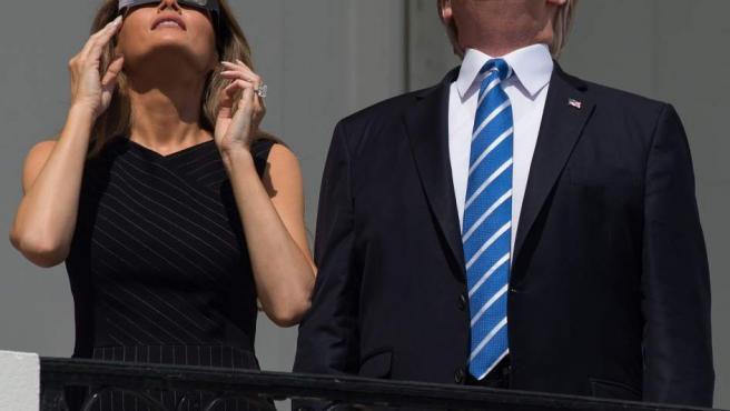 Donald Trump y su esposa Melania observan el eclipse desde el balcón de la Casa Blanca.