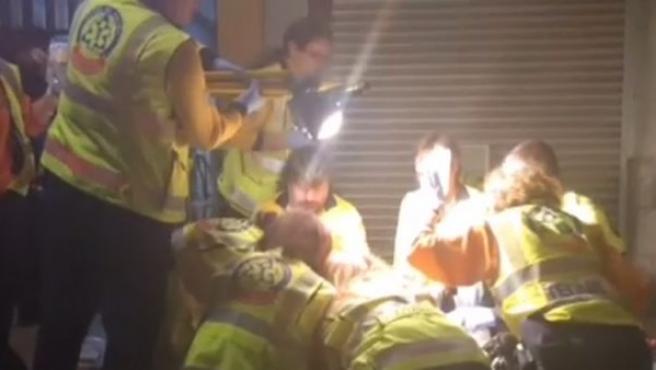 Sanitarios atienden a un hombre que recibió cuatro disparos en una calle del distrito de Usera en Madrid.