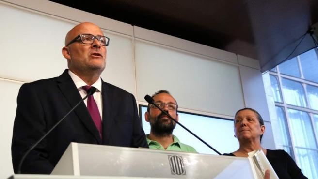 El presidente del grupo parlamentario de JxSí, Lluís Corominas, con los diputados de la CUP Benet Salellas y Gabriela Serra de fondo, antes de presentar la ley de transitoriedad jurídica el 28 de agosto de 2017.
