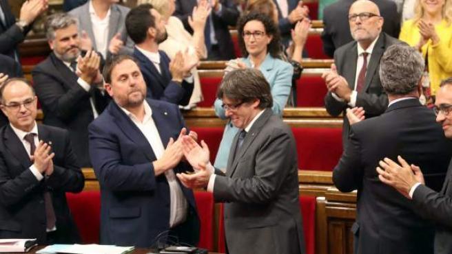 El presidente de la Generalitat, Carles Puigdemont, su gobierno, y el resto de los diputados celebran la aprobación de la ley del referéndum, con los escaños vacios de PSC, Ciudadanos y PPC.