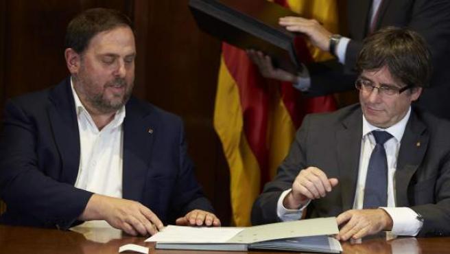 El presidente de la Generalitat, Carles Puigdemont, acompañado por el vicepresidente Oriol Junqueras, firma la convocatoria de referéndum.