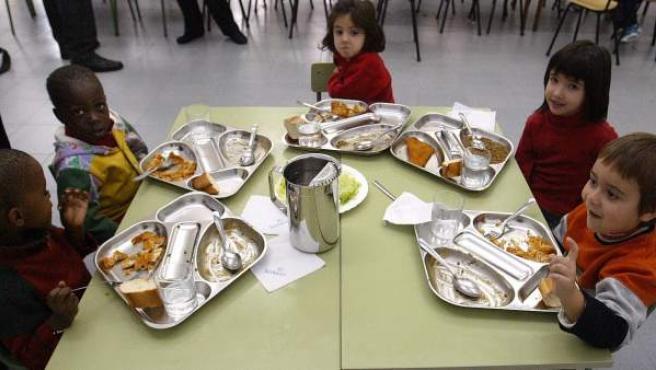 Cuatro niños en el comedor de su centro escolar.
