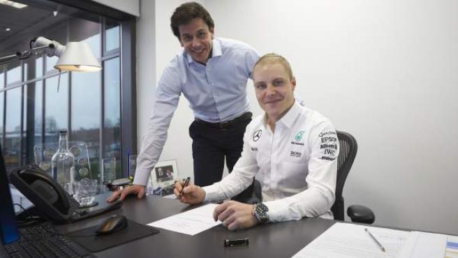 El finlandés Valtteri Bottas, firmando su contrato con Mercedes junto a Toto Wolff.