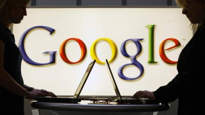 Dos chicas usan sendos ordenadores portátiles frente a un gran logo de Google.