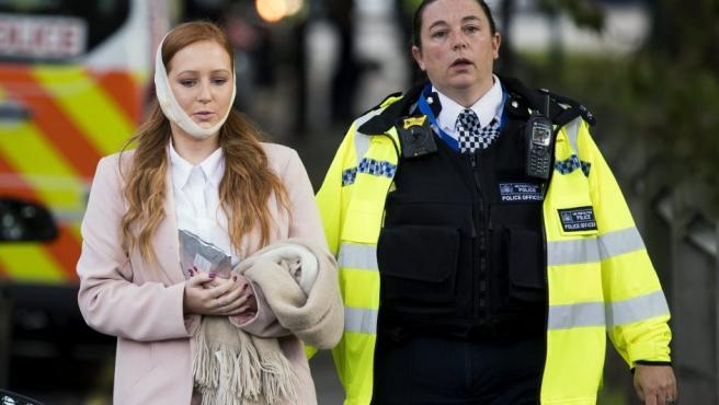 Una agente de policía escolta a una herida en los alrededores de la estación de metro Parsons Green, en Londres (Reino Unido). Varios pasajeros han resultado con quemaduras en el rostro por una explosión en uno de los vagones.