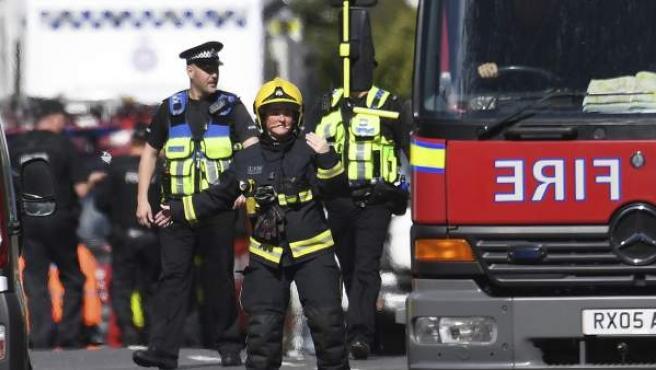 Bomberos y policías caminan junto a la estación de metro Parsons Green en Londres tras la explosión de una bomba.