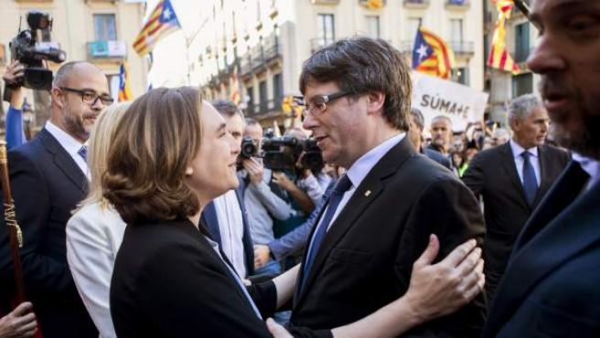 La alcaldesa de Barcelona, Ada Colau (i), saluda al presidente de la Generalitat, Carles Puigdemont (d), durante la concentración de alcaldes en la plaza Sant Jaume de Barcelona.