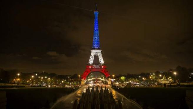 Vista de la torre Eiffel iluminada con los colores de la bandera nacional francesa en París, en homenaje a las víctimas de los atentados perpetrados por el Estado Islámico (EI) en noviembre de 2015.