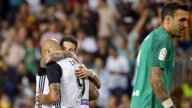 Simone Zaza y Santi Mina se abrazan ante Roberto tras un gol del Valencia al Málaga.