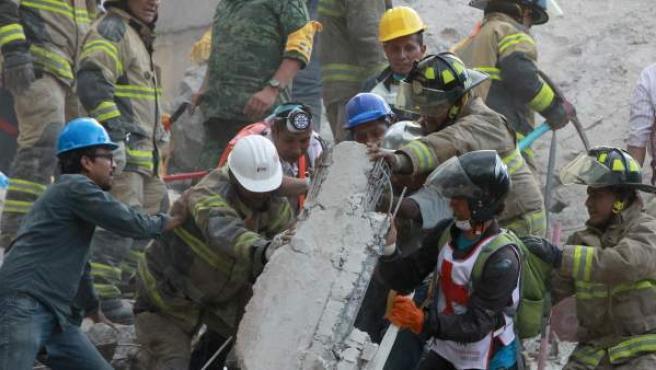 Bomberos mexicanos y rescatistas buscan personas con vida en medio de edificios colapsados en Ciudad de México (México).