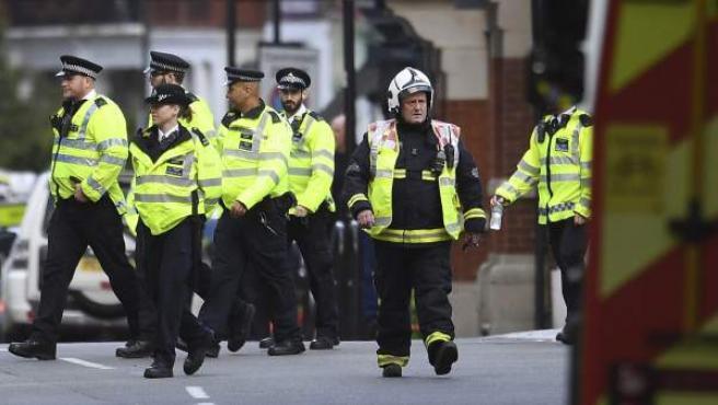 Bomberos y policías caminan junto a la estación de metro Parsons Green en Londres (Reino Unido).