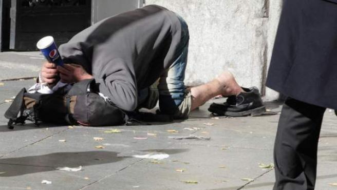 Una persona sin hogar pidiendo en la calle.