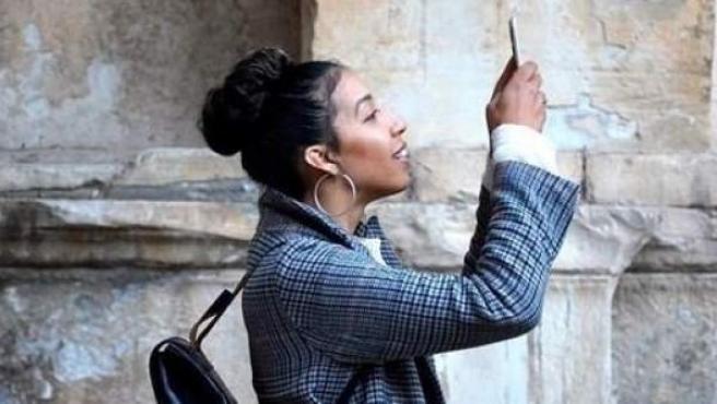 Una joven utiliza su móvil.