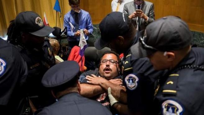 Agentes sacan a una de las personas que se manifestaban en contra del proyecto de ley Graham-Cassidy para revocar Obamacare, en el edificio de oficinas del Senado Dirksen, en Washington DC (EE UU).