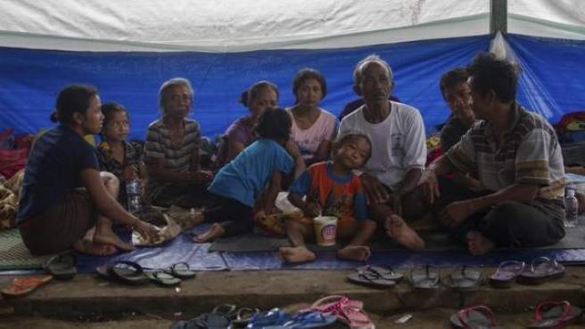 Una familia de evacuados, en el centro comunitario del pueblo Sidemen, que acoge a cientos de personas afectadas por la alerta máxima de erupción volcánica del Monte Agung, en la isla de Bali, Indonesia.