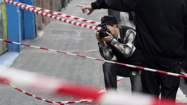 Un ertzaina toma fotografías en la entrada de un domicilio en Vitoria.