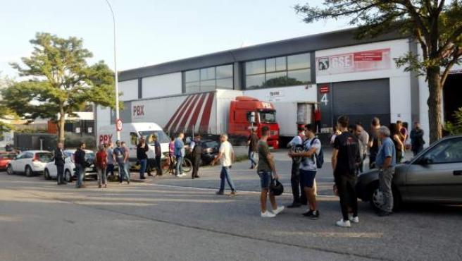 Varias personas en el exterior de la empresa donde la Guardia Civil ha incautado papeletas y urnas.
