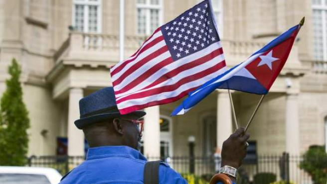Un hombre lleva banderas de Cuba y EE UU.