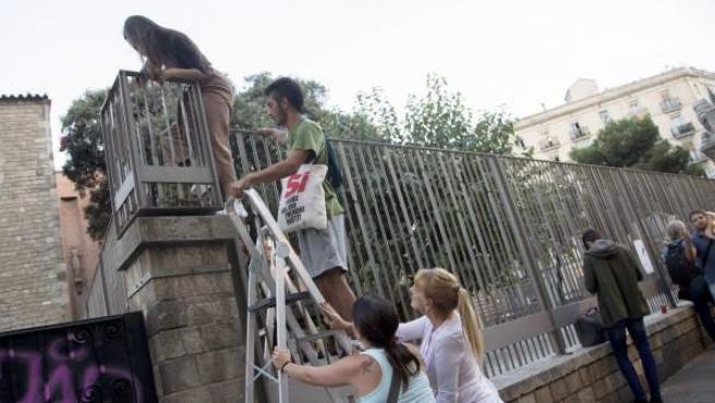 Varias personas entran en el colegio Collaso i Gil de Barcelona tras haber sido cerrado.