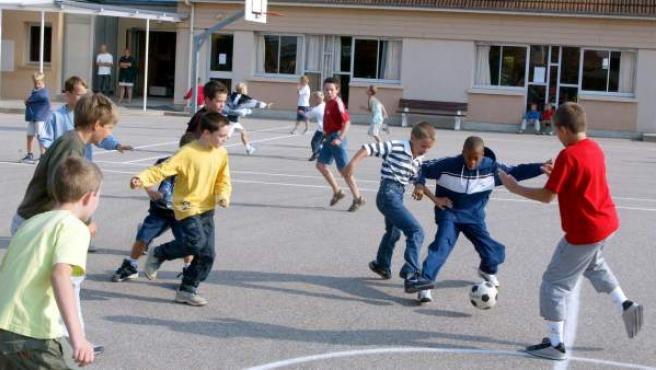 Niños jugando al fútbol en el patio del colegio.