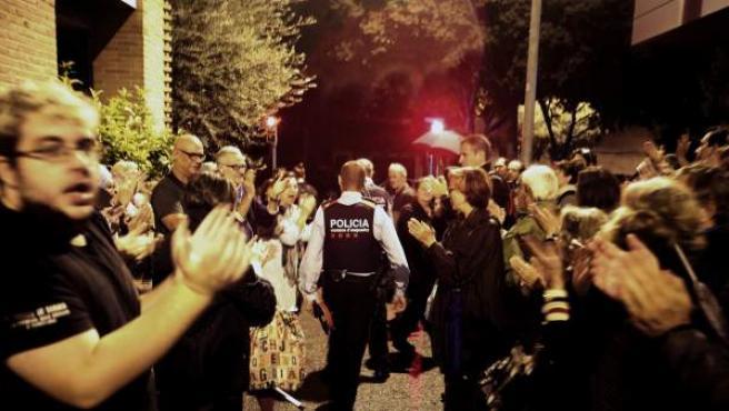 Una pareja de Mossos d'Esquadra salen entre aplausos de una escuela del barrio de Sarriá de Barcelona.