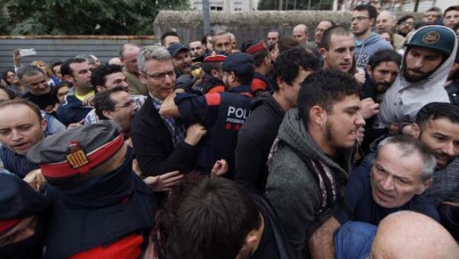 Agentes de los Mossos d'Esquadra intentan acceder al centro donde está previsto que vote el vicepresidente de la Generalitat de Cataluña, Oriol Junqueras, en el referendum independentista del 1-O.