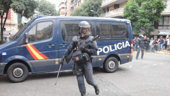Agente antidisturbios actuando en los alrededores del colegio Ramón Llull en Barcelona durante la consulta ilegal de 1-0.