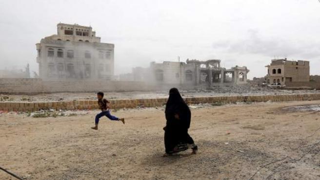 Una mujer y un niño yemení corren para ponerse a salvo mientras la coalición liderada por Arabia Saudí ataca la casa de un líder del movimiento rebelde chií de los hutíes en Saná (Yemen).