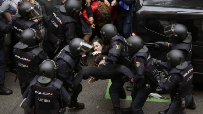 Agentes antidisturbios de la Policía Nacional que han formado un cordón de seguridad trasladan a una joven frente al colegio Ramón Llull de Barcelona.