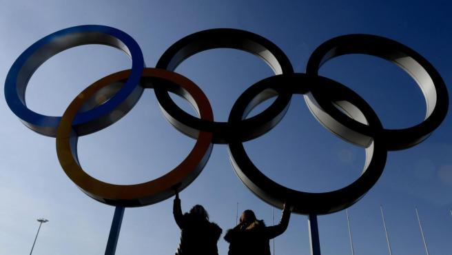 Dos visitantes posan bajo unos aros olímpicos ubicados en la villa olímpica.