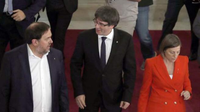El presidente de la Generalitat, Carles Puigdemont, acompañado por el vicepresidente Oriol Junqueras y la presidenta del Parlament, Carme Forcadell, tras el pleno en el Parlament, en Barcelona.