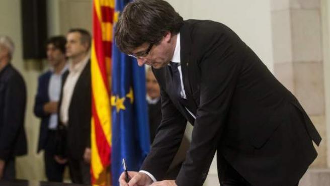 El presidente de la Generalitat, Carles Puigdemont, firma el documento sobre la Independencia después de comparecer ante el pleno del Parlament para trasladar los resultados de la jornada del 1-O,