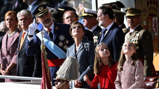 Los Reyes y sus hijas, la princesa de Asturias y la infanta Sofía, observan la exhibición aérea, durante el desfile del Día de la Fiesta Nacional.