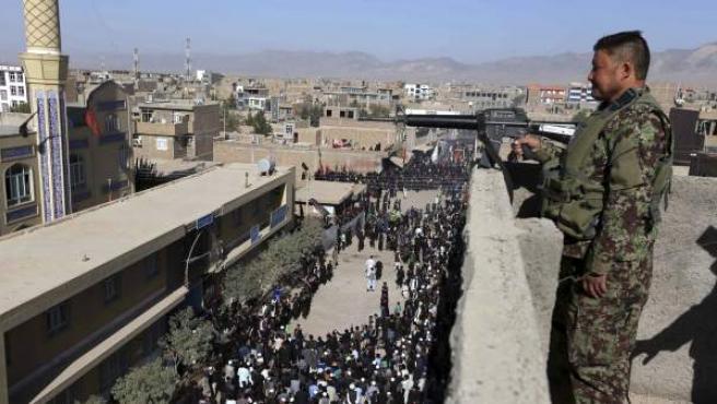Un guarda de seguridad vigila desde la azotea de un edificio durante una procesión chií para conmemorar el Ashura en Herat, Afganistán.