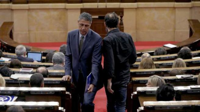 El lider del PPC, Xavier García Albiol, se cruza con el portavoz d ela CUP, Benet Salellas (d), en el pasillo del hemiciclo.
