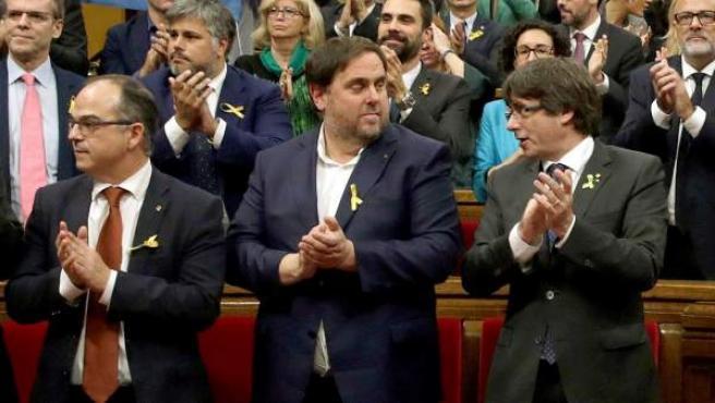 El expresidente de la Generalitat, Carles Puigdemont (d) y el vicepresidente del Govern y exconseller de Economía, Oriol Junqueras (2d), junto a los diputados de JxSí y la CUP y sin los diputados del PSC, PPC y Ciudadanos, aplauden tras aprobarse en el pleno del Parlament, la declaración de independencia.
