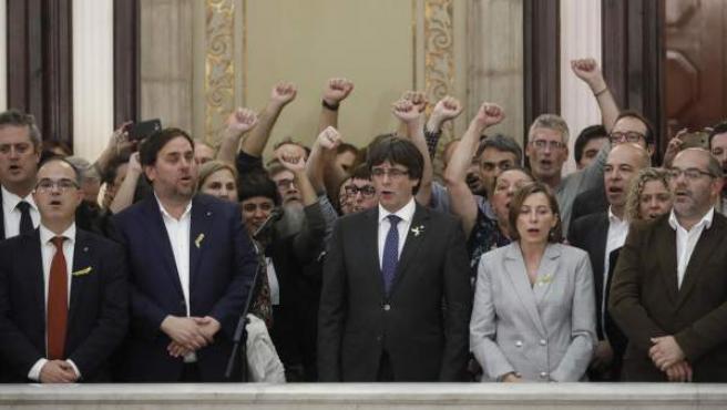 El presidente de la Generalitat, Carles Puigdemont (c) junto al vicepresidente del Govern y conseller de Economía, Oriol Junqueras y la presidenta del Parlament, Carme Forcadell , junto a diputados de la CUP, en las escalinatas del Parlament.
