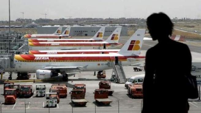Un pasajero observa desde el interior de la terminal varios aviones de Iberia.