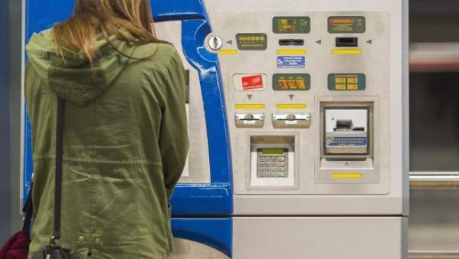 Una usuaria de Metro de Madrid sacando su billete en una máquina expendedora.