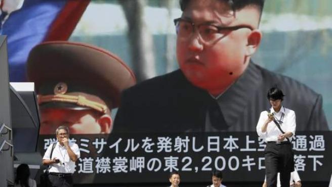Los peatones caminan bajo un monitor a gran escala que muestra al líder norcoreano Kim Jong-un en una emisión de noticias de televisión.