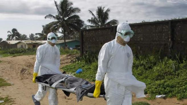 Varios trabajadores sanitarios trasladando a una víctima del virus del ébola en Monrovia, Liberia.