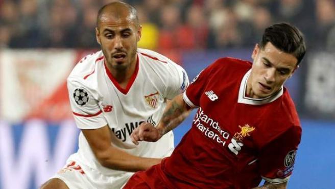 El centrocampista brasileño del Liverpool Philippe Coutinho (d) intenta escaparse del argentino Guido Pizarro, del Sevilla FC